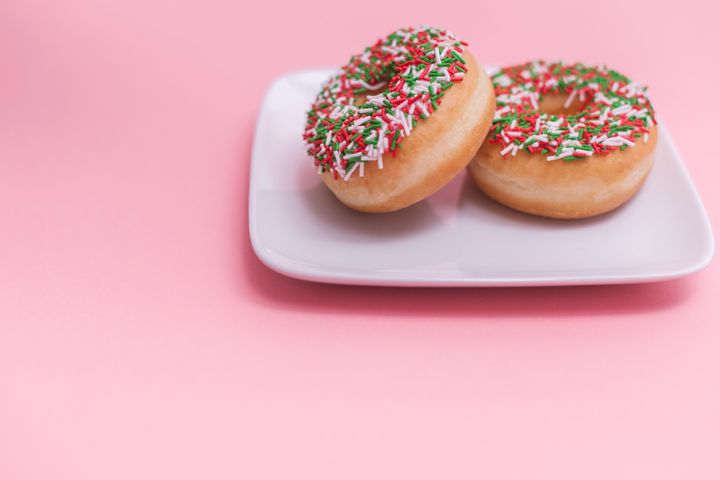 Two donuts with sprinkles on a plate