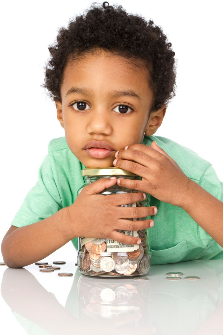 little boy with a jar of money isolated on white background