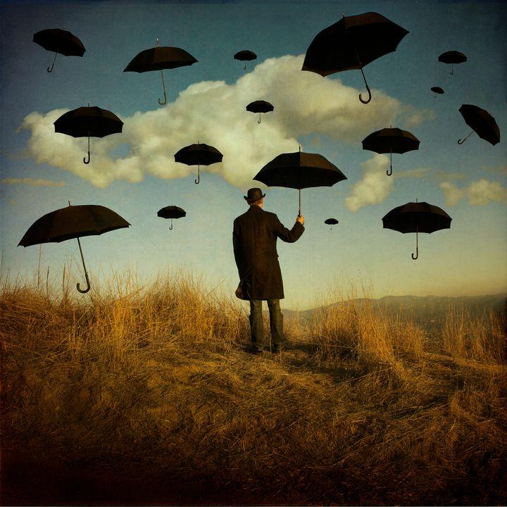 Man holding umbrella against sky.