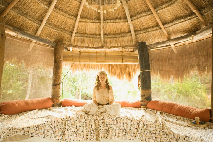 Young woman meditating on bed in hut