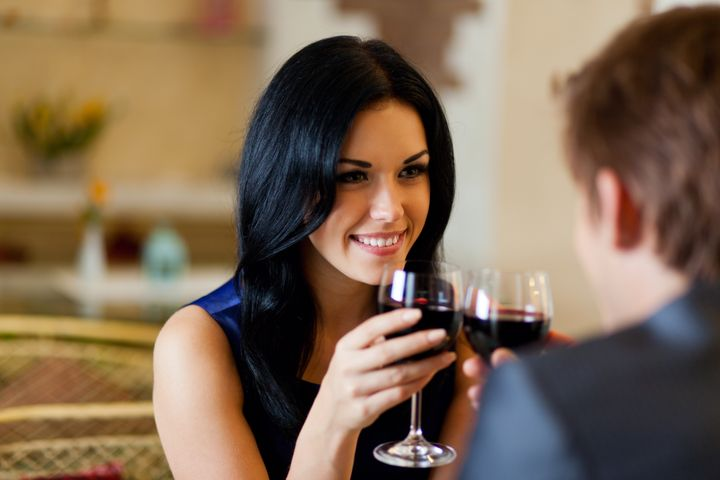 Young happy couple romantic date drink glass of red wine at restaurant, celebrating valentine day
