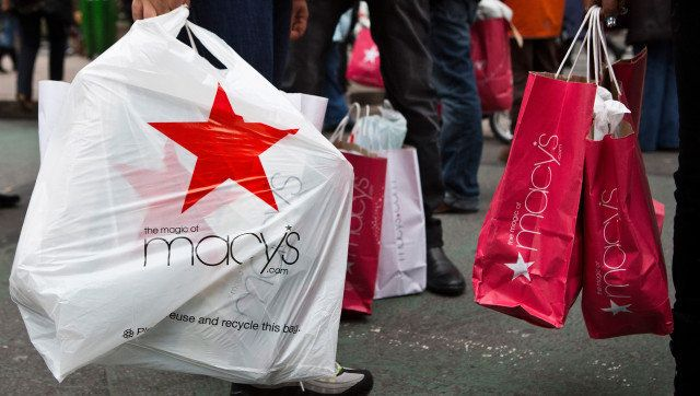 NEW YORK, NY - DECEMBER 26:  People wait to cross the street after shopping at Macy's department store on December 26, 2012 in New York City. Shoppers flooded Manhattan stores for post-Christmas deals throughout the day.  (Photo by Andrew Burton/Getty Images)