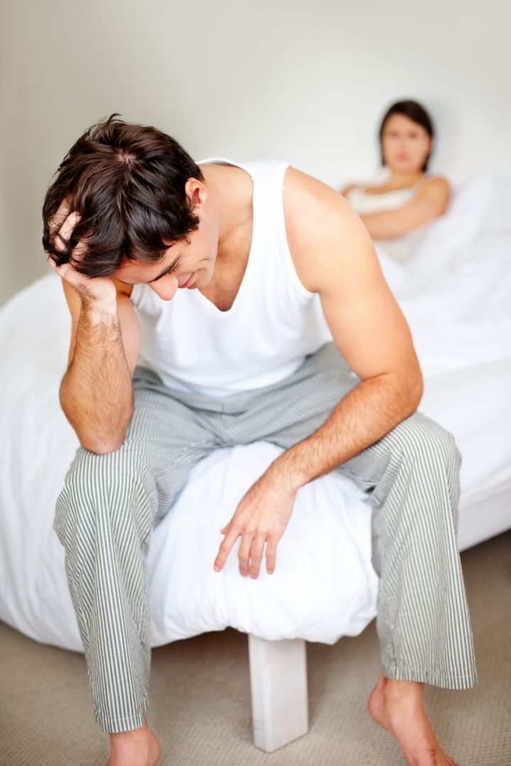 Frustrated young man sitting after having an argument with his wife in bedroom