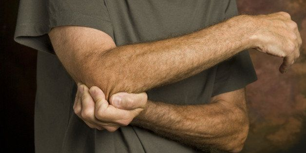 closeup of man massaging elbow