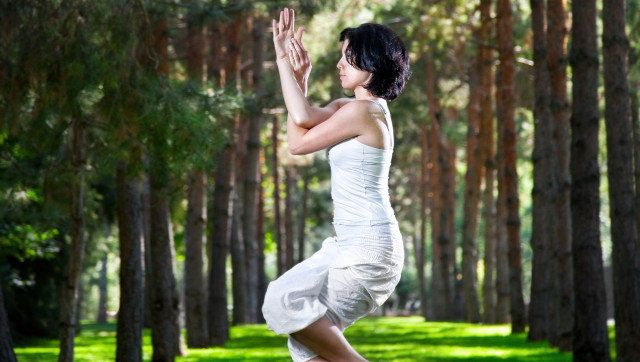Yoga garudasana eagle pose by woman in white costume on green grass in the park around pine trees