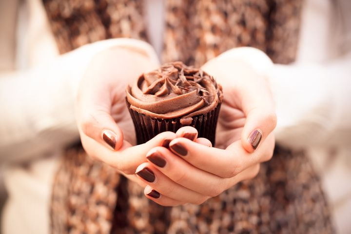 Girl holding chocolate cupcake in hands wearing leopard print scarf and brown nail polish.