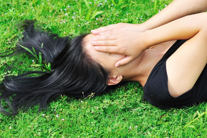 depress woman on green grass