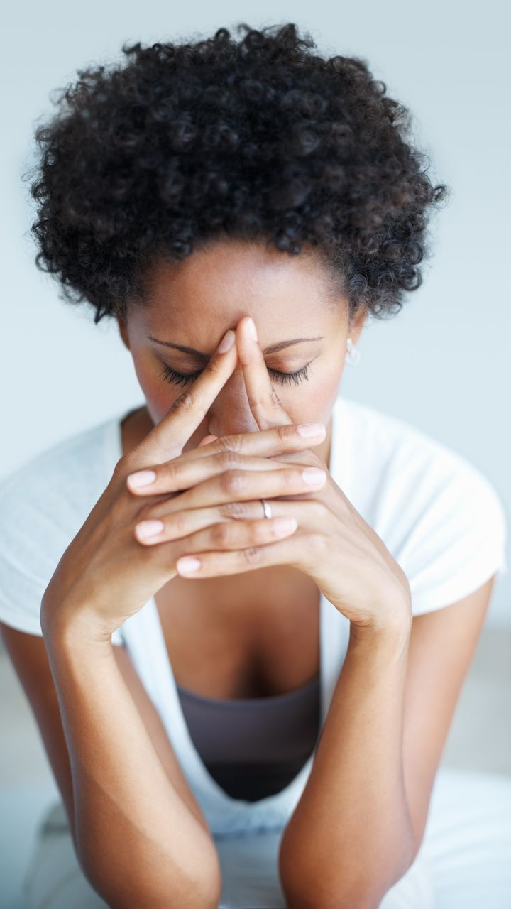 Portrait of African American woman suffering from illness or headache