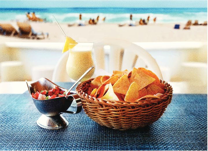 Stipple engraving of tortilla chips with salsa and a pina colada at a luxury tropical resort.