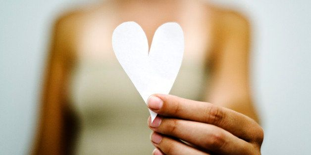 Woman's hand holding out paper heart