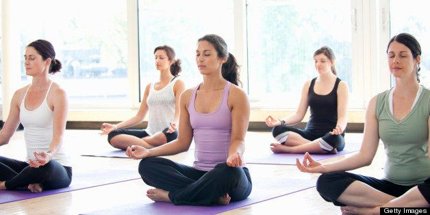 Class of women performing the meditative Sukhasana pose in a bright, modern yoga studio.