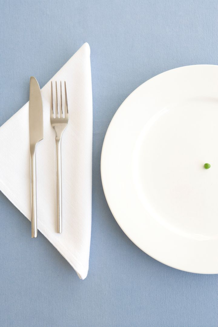 Place setting with green pea in center of plate, overhead view
