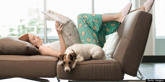 25yr. Cauc woman in pajama bottoms and camisole, laying on couch as she reads newspaper, Jack Russell terrier laying next to her