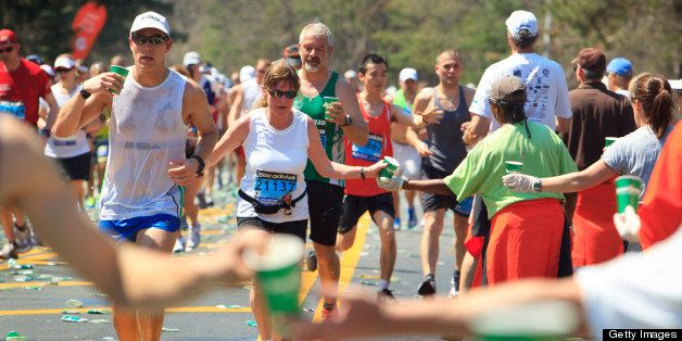 WELLESLEY, MA - APRIL 16: Boston Marathon runners at the half-way water station in Wellesley coped with the staggering heat the best they could - by dousing themselves with water. (Photo by Dina Rudick/The Boston Globe via Getty Images)