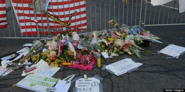BOSTON - APRIL 17: Signs, flowers and candles make up a makeshift memorial at the corner of Berkeley and Boylston Street  for the victims of the Boston Marathon bombing April 17, 2013 in Boston, Massachusetts. Boston continues to get back to normal, as businesses and streets are reopened following a two bomb explosion at the finish line of the marathon that killed 3 people and injured hundreds more. (Photo by Darren McCollester/Getty Images)