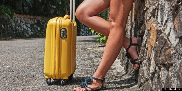 female feet with yellow suitcase