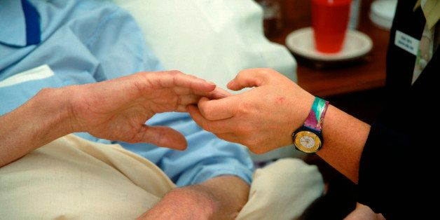 Hospice worker holding elderly man's hand UK. (Photo by: Photofusion/UIG via Getty Images)