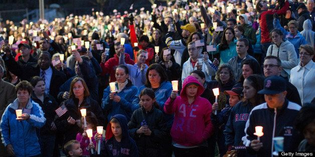 Mourners hold candles and U.S. flags during a vigil for Martin Richard, one of three killed in the Boston Marathon bombings, at Garvey Park in Boston, Massachusetts, U.S., on Tuesday, April 16, 2013. Richard, an 8-year-old from Boston's Dorchster neighborhood, was among the dead in blasts that also injured his mother and sister. Photographer: Scott Eisen/Bloomberg via Getty Images