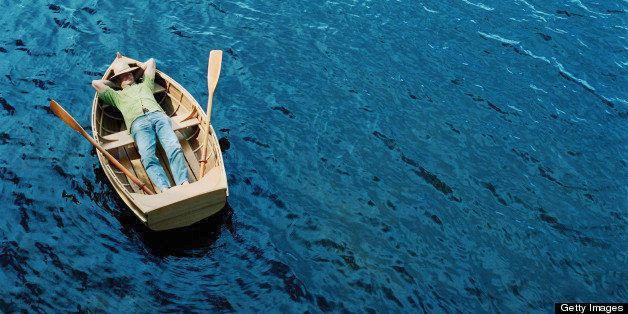 Man lying down in rowing boat, elevated view