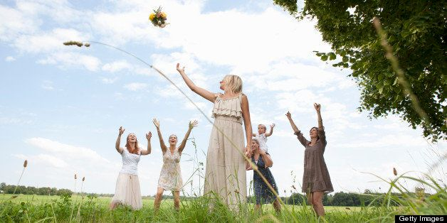 Bride tossing bouquet to wedding party