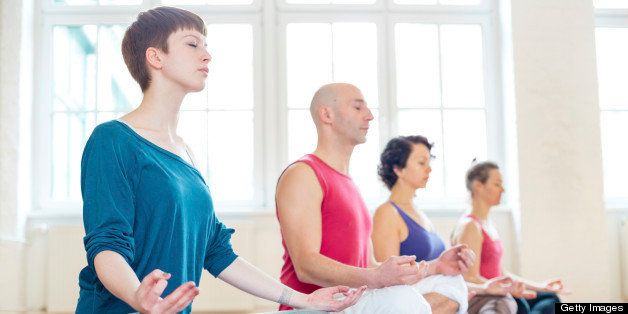 Group of people practising the yoga lotus position
