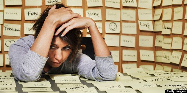 Woman at desk surrounded in adhesive notes, head in hands