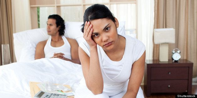 Upset couple sitting on the bed separately after an argument