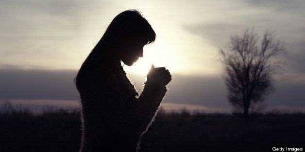 Silhouette woman praying  outdoors in field with single tree.
