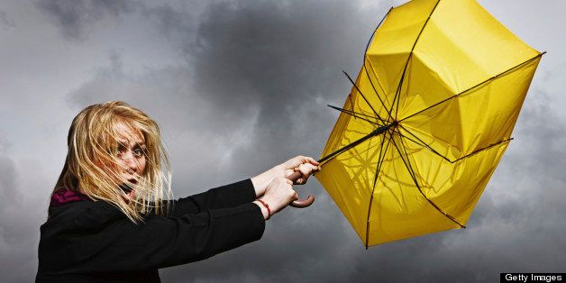 A pretty blonde woman looks horrified and helpless as her frayed and broken umbrella blows away from her, dragging her along, in a thunderstorm.