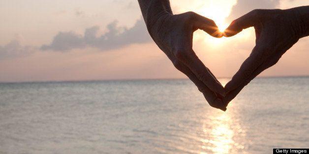 Detail of woman's hands making heart shape, sea