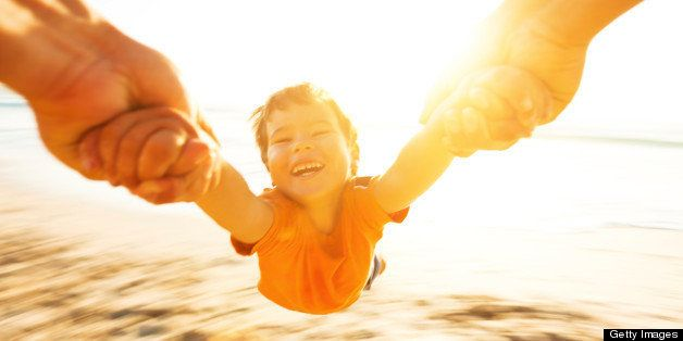Happy boy spinning around his father on a beach. Motion blur.