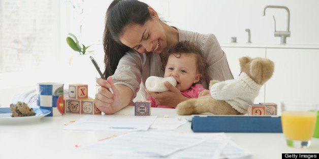 Hispanic woman working and holding baby daughter