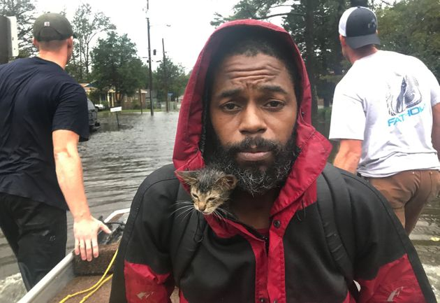 Survivor the kitten huddles inside Robert Simmons Jr.'s jacket as the pair flee rising waters in New...