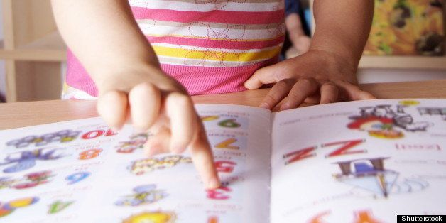 Little Girl Learning Figures and Letters with Picture Book
