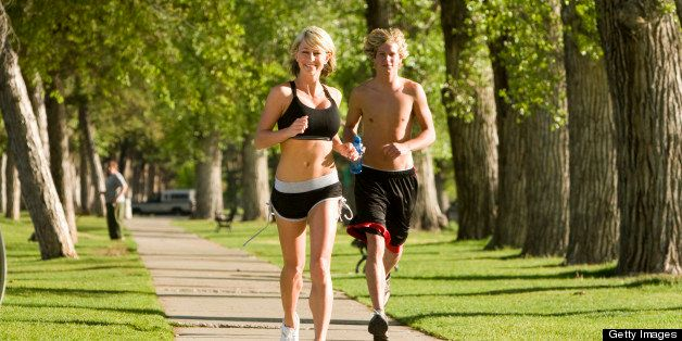 Young couple running outside in park