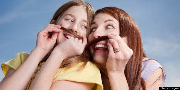 A mother and her daughter being silly together making mustaches out of their hair.