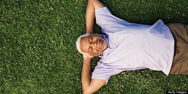 Senior man lying down on grass