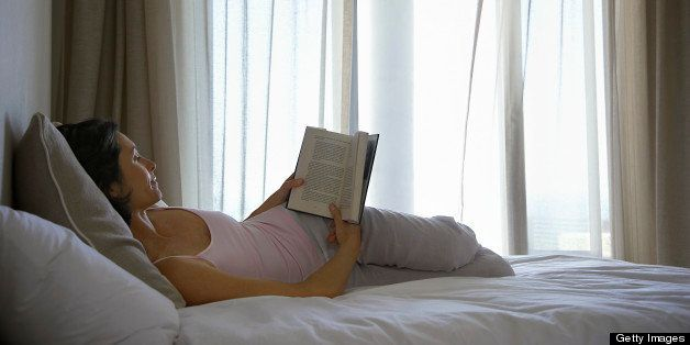 Woman reading book, lying on bed