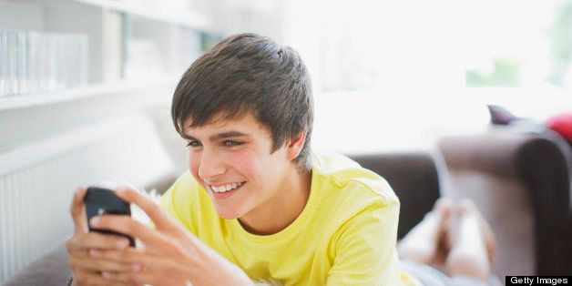 Smiling teenage boy in living room text messaging on cell phone