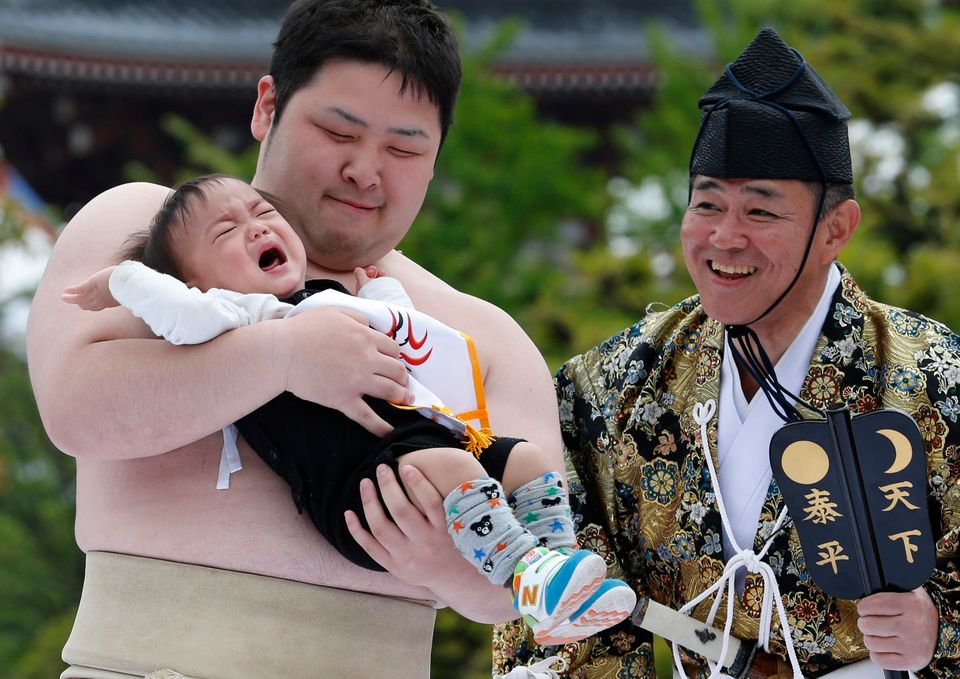An unidentified baby, held by a college sumo wrester, cries during Naki Sumo, or Crying Baby Contest, as a judge looks on at