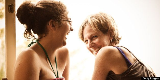Mother and teenage daughter laughing in front of open balcony.