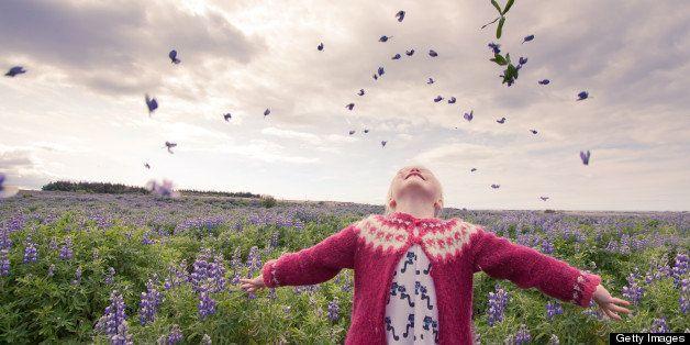 Girl throwing flowers up in air.
