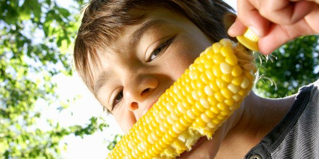 A boy enjoying corn on the cob outside in the summer sunshine.