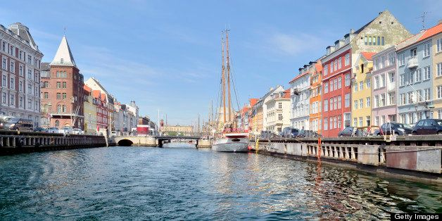 Looking down one of the many branches of the Nyhavn canal in Copenhagen with colorful buildings lining the streets against a clear sky.