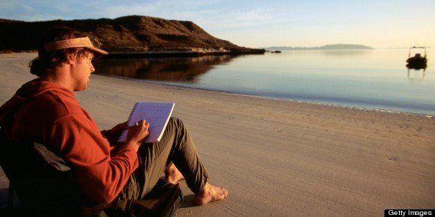 Man sitting on beach writing in journal.