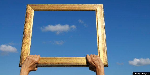 Woman holding an old frame against a blue cloudy sky. Blurred background