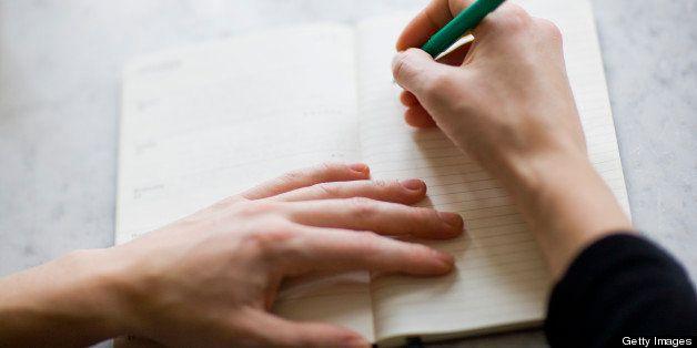 Woman writing on diary