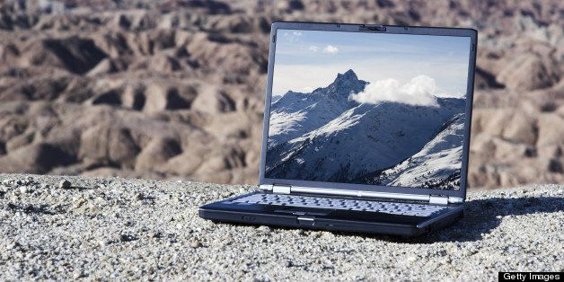 Global warming concept. A modern laptop computer sits in a desert landscape with snow covered mountains on the screen. All logos have been removed.