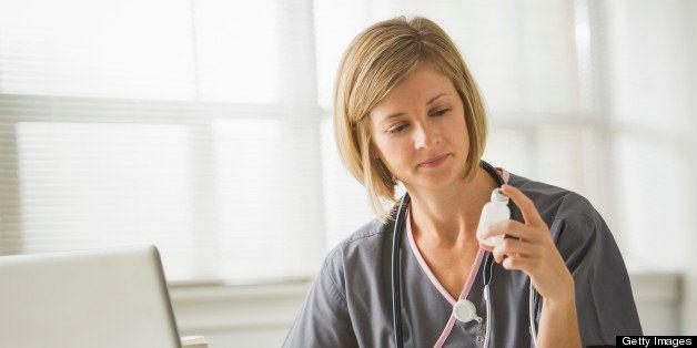 Caucasian nurse looking at medicine bottle