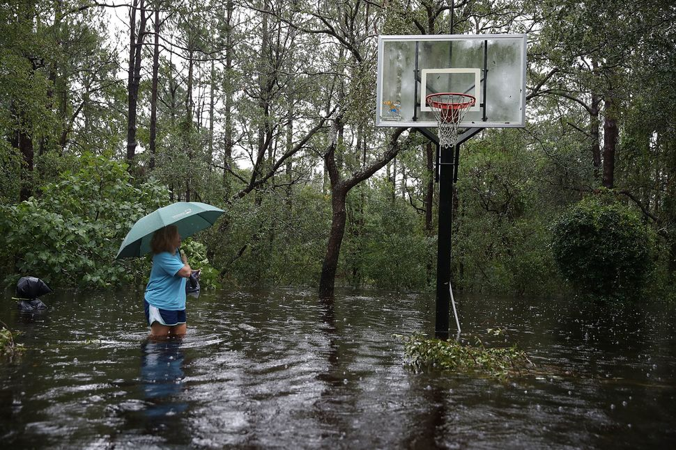 Kim Adams makes her way to her home that is surrounded by flood waters in Southport, North Carolina.